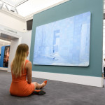 LONDON, ENGLAND - SEPTEMBER 08:  A member of the Sotheby's auction house staff poses in front of  'Blue Sauna' by Adriana Varejao (estimated sale price £400,000-600,000) at the press preview of the 'Shake It Up Online' auction of works from the private collection of photographer Mario Testino on September 8, 2017 in London, England. Running from 1-15 October, the online auction sees over 300 works from a wide range of artists being placed on sale.  (Photo by Leon Neal/Getty Images)