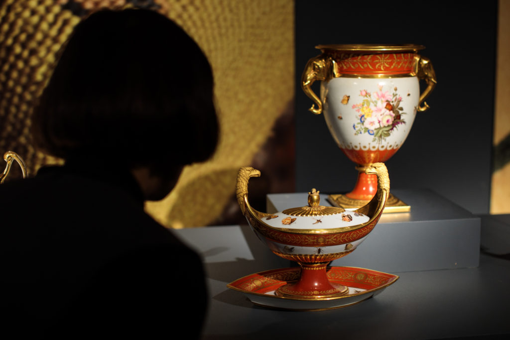 LONDON, ENGLAND - FEBRUARY 20: An employee poses with pieces from the 'Marly Rouge' porcelain service set made for Napoleon I, circa 1807-1809 (estimate $150,000 - 250,000) during a photocall for the Peggy and David Rockefeller art collection at Christies auction house on February 20, 2018 in London, England. Christies unveiled today highlights from the Rockefeller collection ahead of the New York auction on May 7th which is expected to raise in excess of $500M, the proceeds from which are to be donated to established charities. (Photo by Jack Taylor/Getty Images)