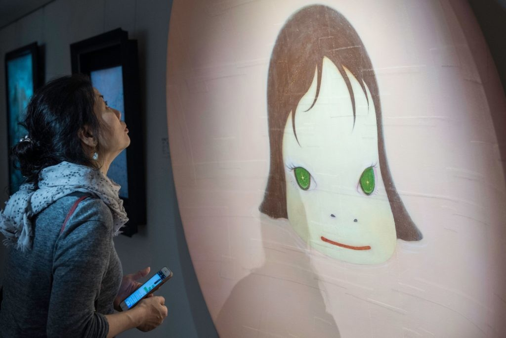A woman looks at Japanese artist Yoshitomo Nara's 'In the Pinky Lake' during a media preview of Christie's Hong Kong Spring Sales in Hong Kong on March 30, 2018. / AFP PHOTO / Philip FONG / RESTRICTED TO EDITORIAL USE - MANDATORY MENTION OF THE ARTIST UPON PUBLICATION - TO ILLUSTRATE THE EVENT AS SPECIFIED IN THE CAPTION / The erroneous mention[s] appearing in the metadata of this photo by Philip FONG has been modified in AFP systems in the following manner: [adding restriction -RESTRICTED TO EDITORIAL USE - MANDATORY MENTION OF THE ARTIST UPON PUBLICATION - TO ILLUSTRATE THE EVENT AS SPECIFIED IN THE CAPTION]. Please immediately remove the erroneous mention[s] from all your online services and delete it (them) from your servers. If you have been authorized by AFP to distribute it (them) to third parties, please ensure that the same actions are carried out by them. Failure to promptly comply with these instructions will entail liability on your part for any continued or post notification usage. Therefore we thank you very much for all your attention and prompt action. We are sorry for the inconvenience this notification may cause and remain at your disposal for any further information you may require.        (Photo credit should read PHILIP FONG/AFP/Getty Images)